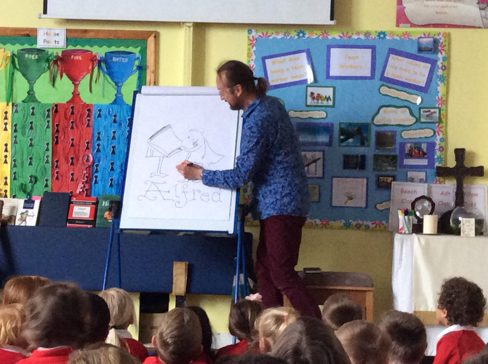 Marc Vyvyan-Jones drawing the young Alfred during a 'Draw like a Saxon' Illustrator Visit to Upton Noble Primary School, Somerset.