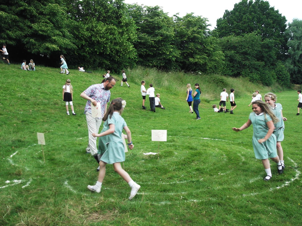 Celebrating a Midsummer tradition at Wiveliscombe Primary School - Marc Vyvyan-Jones made a mizmaze from flour, then the children took turns running around it, and making a wish in the middle.