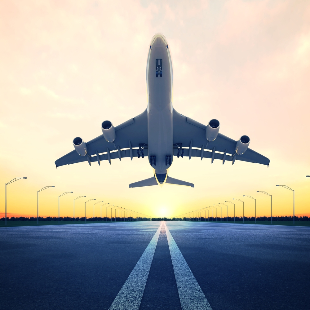 stock-photo-airplane-at-takeoff-seen-from-the-bottom-in-the-airport-landing-strip-at-sunset-57056986.jpg