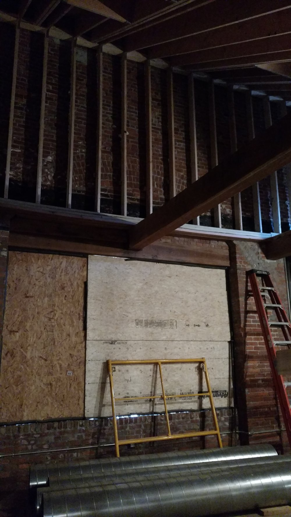 Living space of third floor two-bedroom – outline of what used to be the church's rose window can be seen behind ladder and metal framing