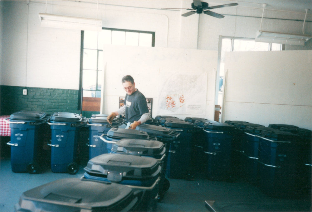 After the first cans were distributed, WBNA applied for United Way and Citizens Bank grants for multiple, successive rounds of bulk trash container purchases. Neighbor Vinny Bucci readies the 45 gallon cans during a pick-up event (2001)