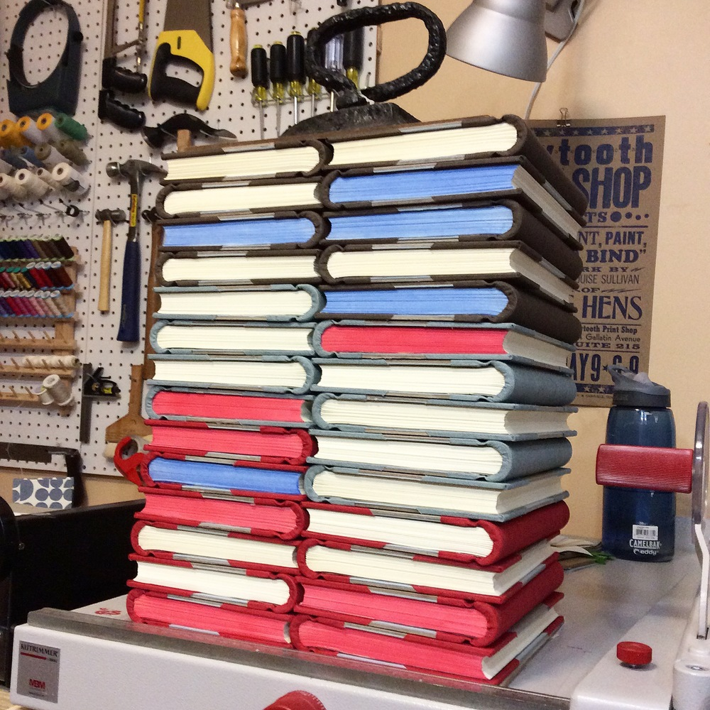 A stack of new springback journals drying underweight, waiting for their decorative papers.