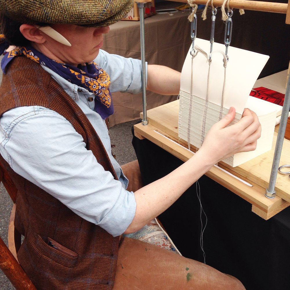 Watch me bind books the same way it was done in the Victorian Era, on a book sewing frame! Find me in the Artisan Village by the