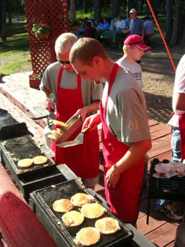 Camp Staff at Lee Valley cooking a delicious breakfast as Dick Borrud looks on from a distance.