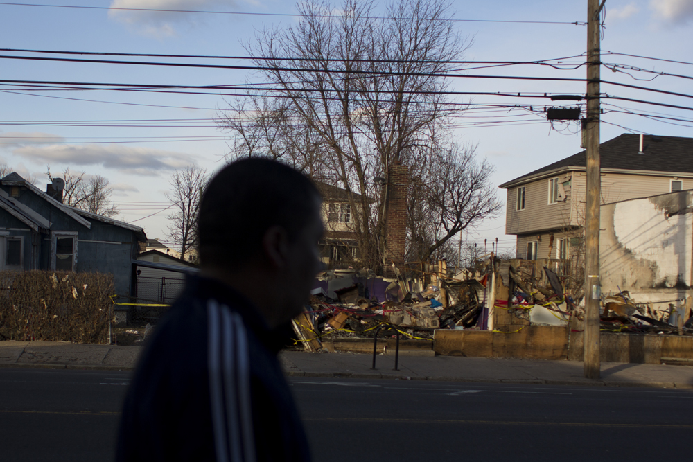 José Parra, 39, walks past the ruins of a house that burnt down on the night of Hurricane Sandy.