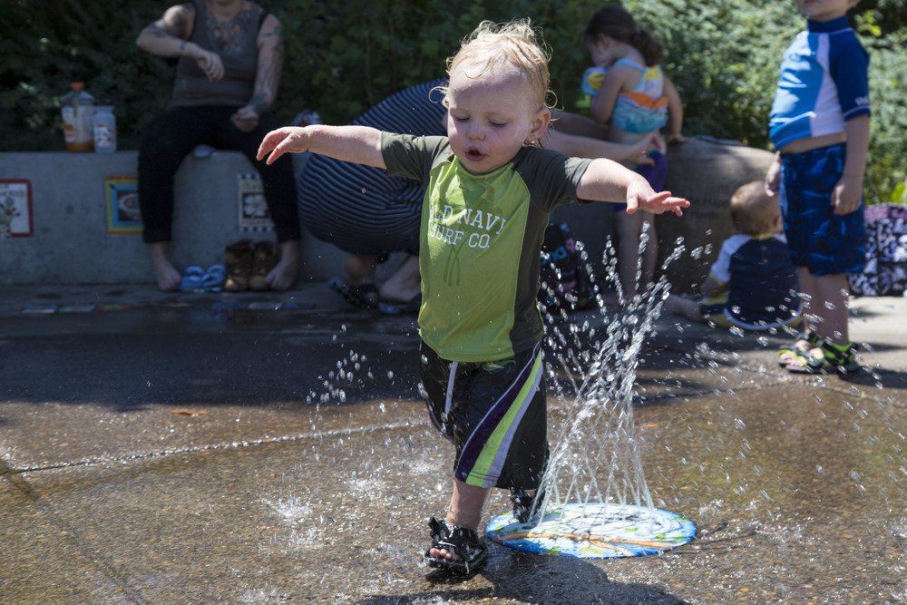 Oliver runs through the water feature at Washington Park during record-high temperatures in Eugene.