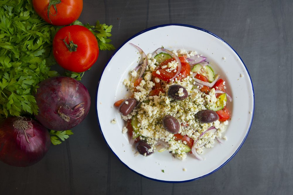 The typical Greek salad, also commonly know as Choriatiki (Χωριάτικη), consists of tomatoes, onions, cucumbers, olives, feta cheese, oregano and extra virgin olive oil.