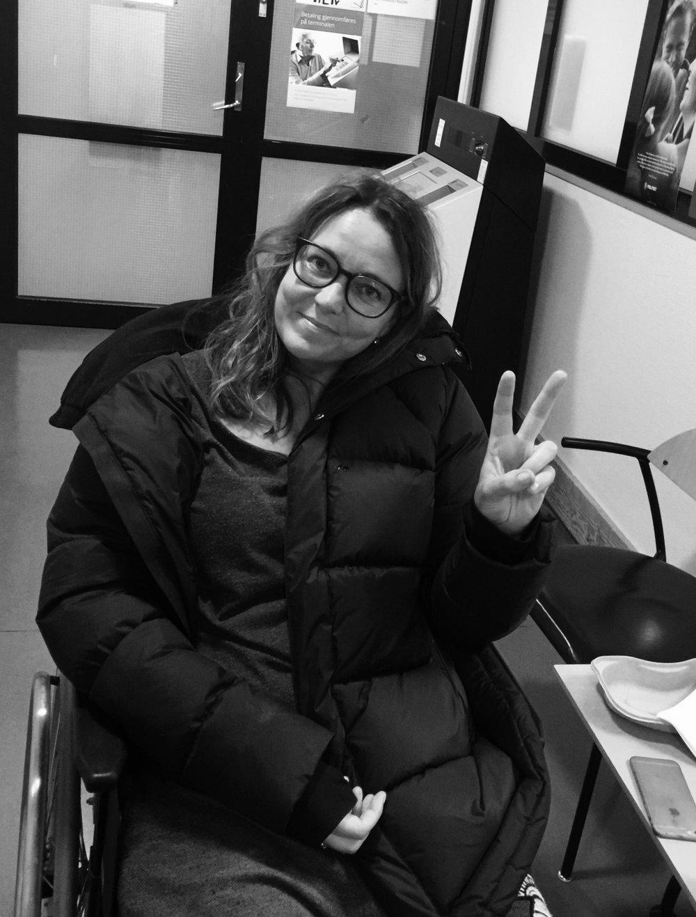 På legevakten på tampen av 2016: Smertetårene er tørket opp. Jeg får en rullestol å sitte i, og smiler tappert mens jeg gjør V-tegnet.