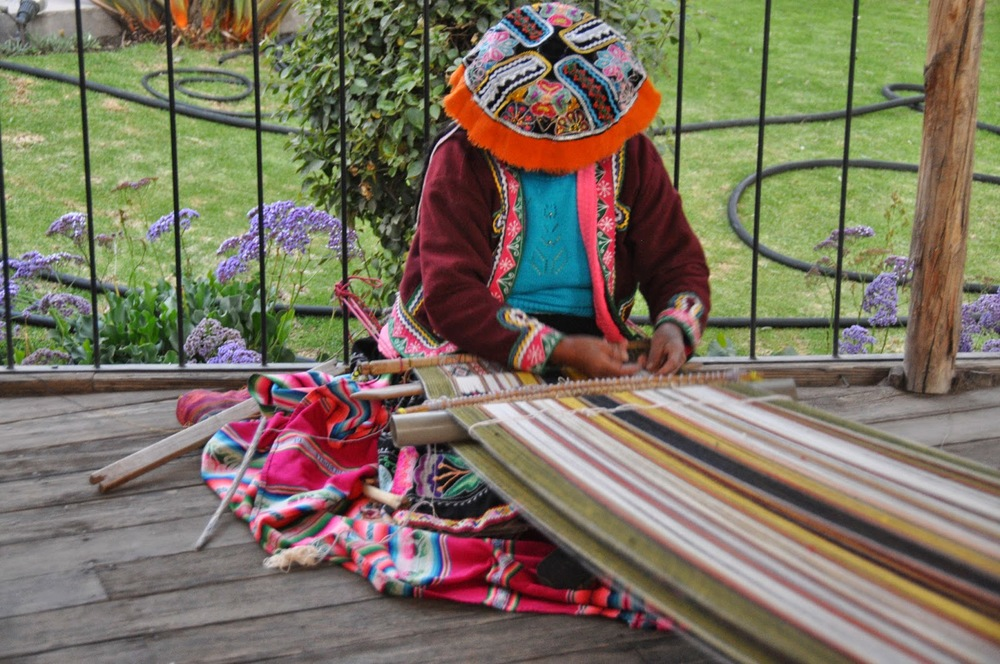 This woman is demonstrating the traditional style of Peruvian weaving.