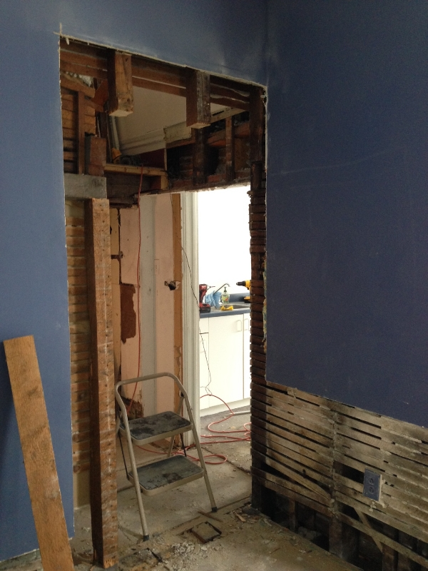 """A new opening from the rear office to the new lunchroom. It's amazing how a few lines moved on a drawing can create such a bloody mess! Check out the full 4""""x4"""" studs! Opening up this wall reveals how uneven floors are from one room to the next. We will continue to put on our creative thinking caps to make it all flow smoothly."""