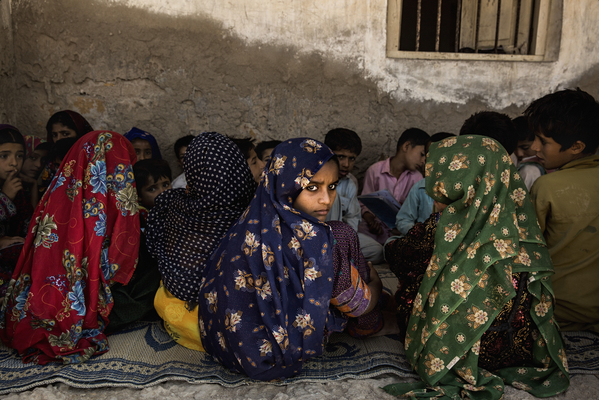 Students in the coastal fishing community of Haji Karfoor Jat gather for lessons in the shade outside their schoolhouse, which is collapsing due to erosion caused by saline groundwater. Temperatures here can exceed 45 °C in peak summer.