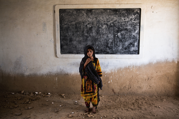 Six-year-old Gul stands amid the ruins of her classroom in Haji Karfoor Jat. The school's walls and ceiling are collapsing due to erosion by saline groundwater and salt winds blowing from the nearby Arabian Sea.