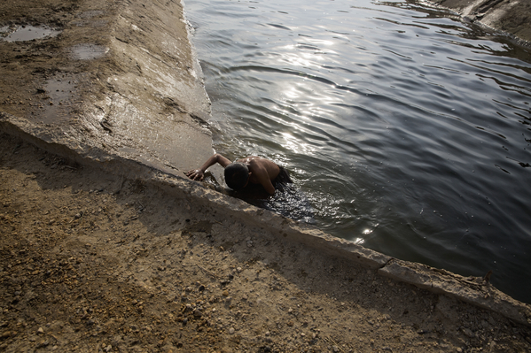 A boy climbs out of the canal after a swim in Noor Muhammad Thaheem. The canal is the only source of non-saline water accessible to villagers for their homes. This untreated water is used for bathing as well as cooking and drinking.