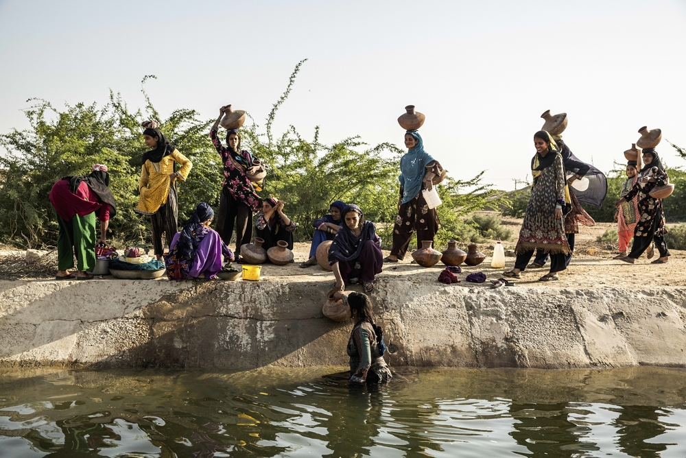 Women collect water from the open canal in Noor Muhammad Thaheem.