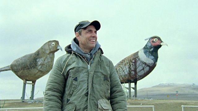 "Gary Greff in front of ""Pheasants on the Prairie"". Which consists of a 40-foot tall rooster, a 35-foot tall hen and two chicks that reach 15 feet high. Weighing in together at a whopping 30,000 pounds."