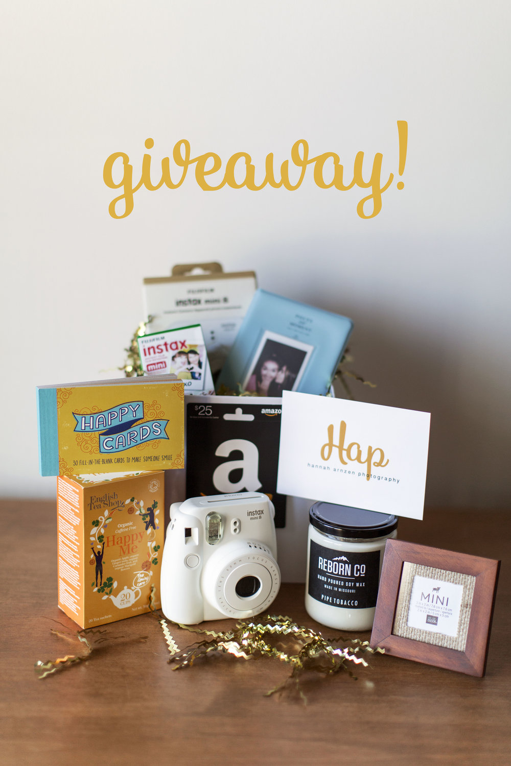 Giveaway items include the following: A BRAND NEW Fujifilm instax mini 8 camera, colored film for the instax mini 8, (1) photo album for your polaroids, (1) $25 gift card to Amazon, (1) HAPPY CARDS book, (1) box of organic Happy Me tea, (1) Pipe Tobacco soy wax candle from REBORN CO, (1) $50.00 gift certificate towards a HAP photo session, and (1) wooden photo frame with YOUR entry photo!