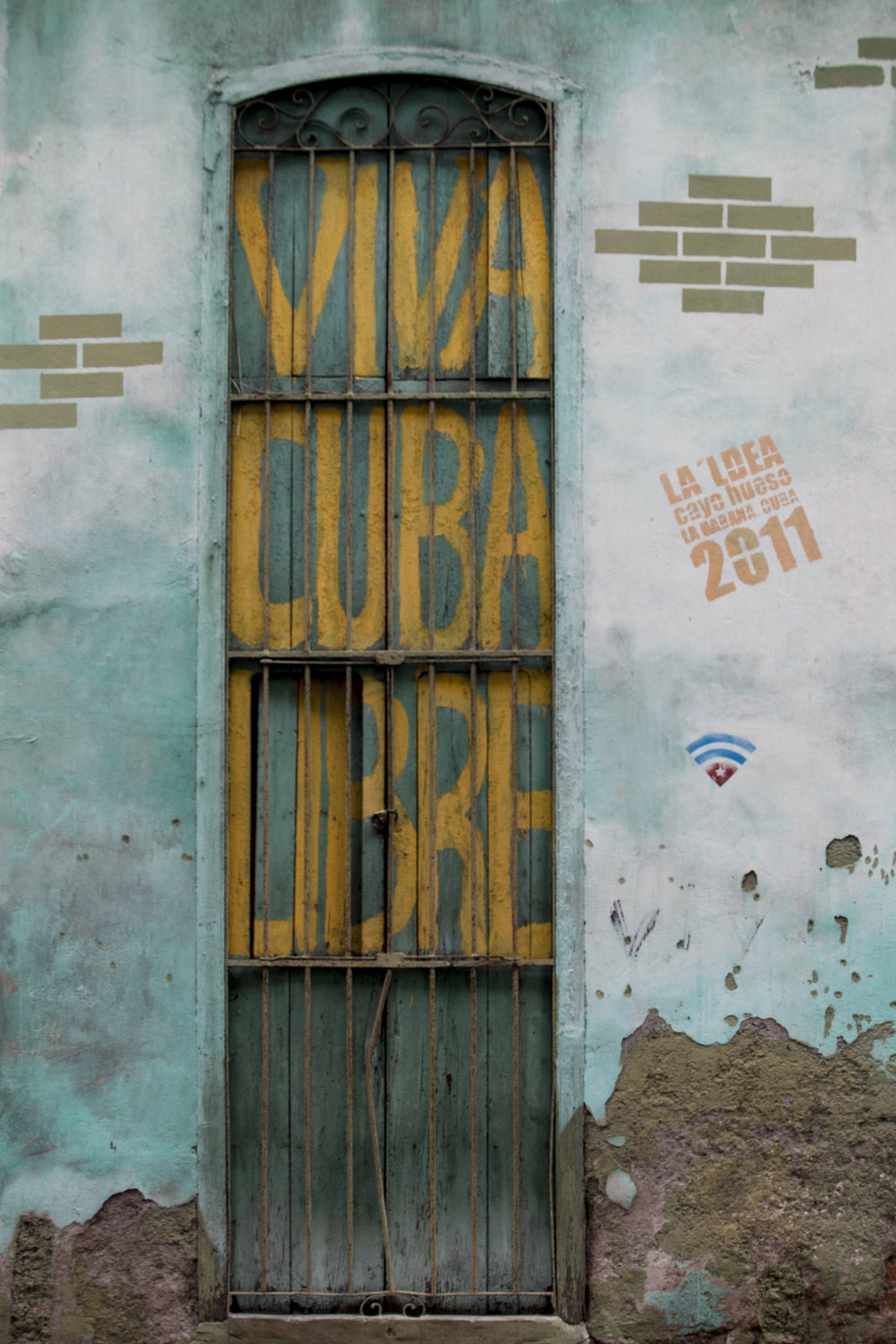 "VIVA CUBA LIBRE    ""Long Live Free Cuba"", a sentiment that dates back to the 1959 Revolution led by Fidel Castro, Raúl Castro and Che Guevara, paints the streets from the cities to the pueblos. Whether the saying has undergone semantic satiation is unknown. Gracing walls, billboards, and rural roadsides, words of the revolution era remain a significant part of everyday environments in Cuba. As we wandered the streets, we questioned whether the repetition has removed some of the original meaning or instead instilled a greater sense of national pride."