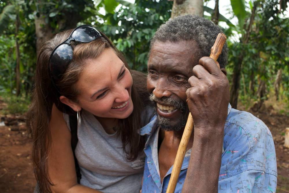 Amy with a village gentleman whose mud house was repaired by Kupendwa.