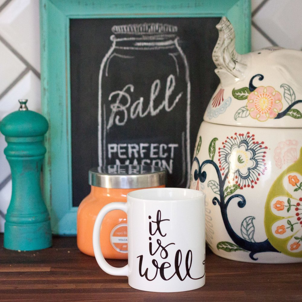 "The new ""It Is Well"" mug wraps around with a cross connecting the words."
