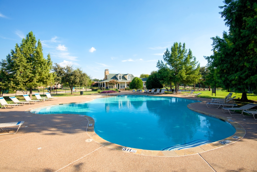 "The community pool area is open May until October. The larger pool has a maximum depth of 5'6"" with multiple step entrances and a rocky shallow foot splash space. The pool lights up at night for moonlight swimming."