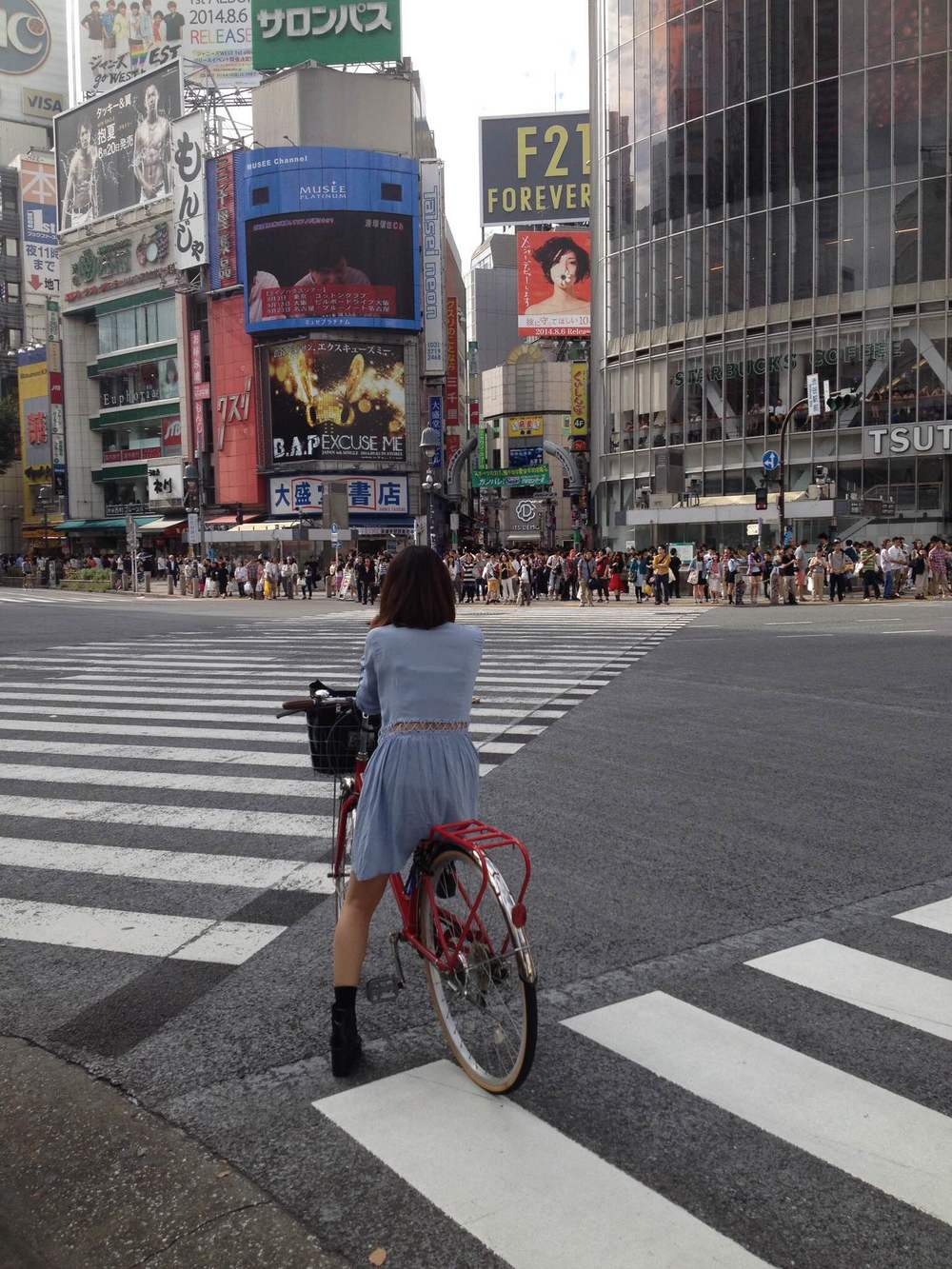 A girl on a bicycle at Shibuya's famous crosswalk, daring to wait in the road for the light to turn