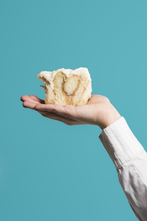 Food Photography of a cinnamon roll in profile held palm up on a hand in a blue background. Utah Copyright 2016 InTheLoupePhotography