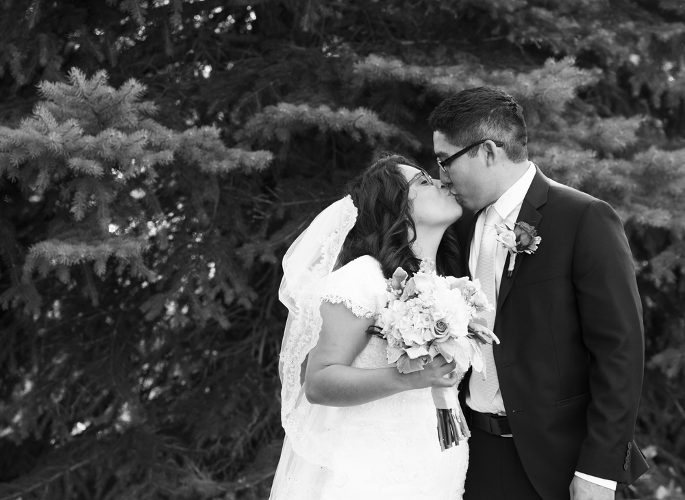 Black and White Photo of the Bride and Groom kissing in profile while the bride holds her bouquet.  Timpanogos Utah Copyright 2016 InTheLoupePhotography