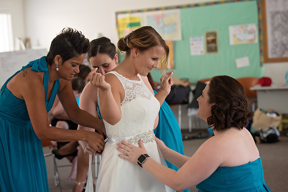 Beautiful moment between Mallory and her Matron of Honor, Jennifer, as her bridesmaids help her get into her wedding gown