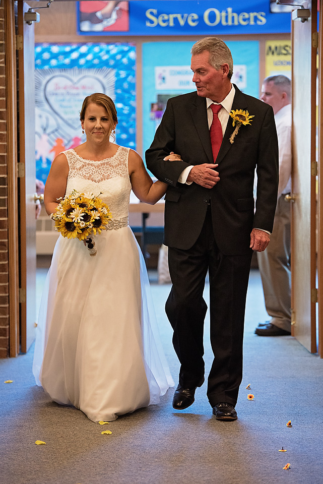 Mallory's father stealing a glimpse of his daughter as he leads her down the aisle to her groom