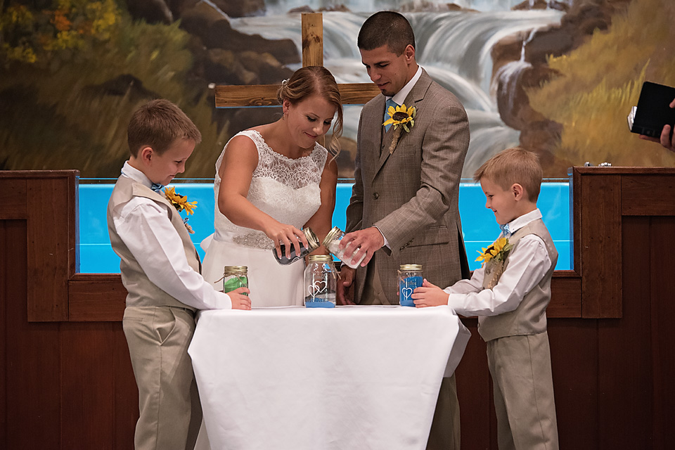 As a sign of unity of Mallory & Charlie with her two sons, they each poured a different color sand into a jar to represent their new family.