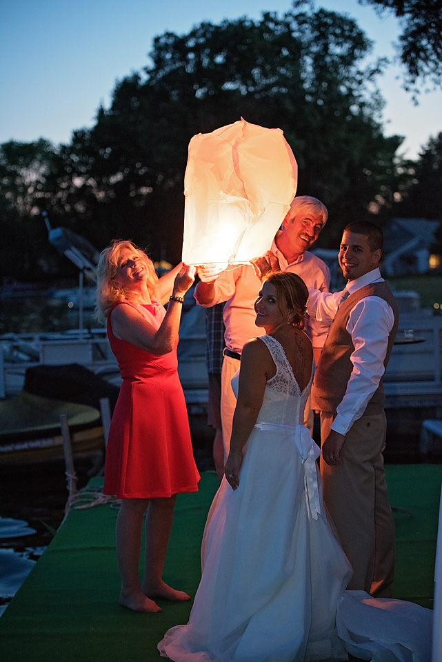 Mallory and Charlie lighting a floating lantern with the Anniversary dance winners, Therese & Dave