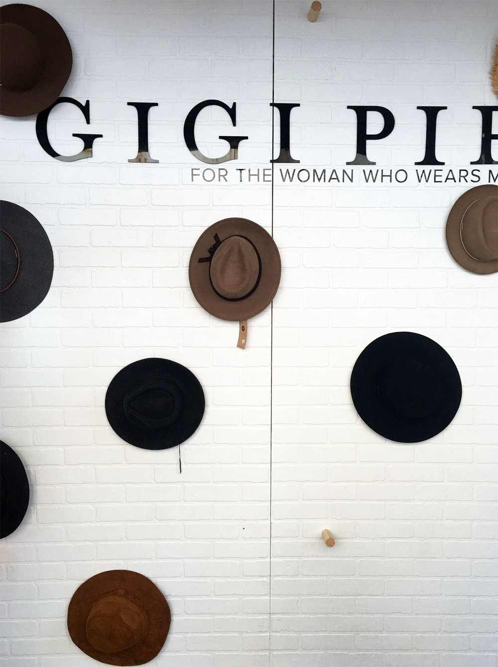 "One of my favorite booths at Spring at the Silos was Gigi Pip's fresh set up. This white brick wall housing a selection of hats and the Gigi Pip tagline ""for the woman who wears many hats"" is a detail you've gotta love."