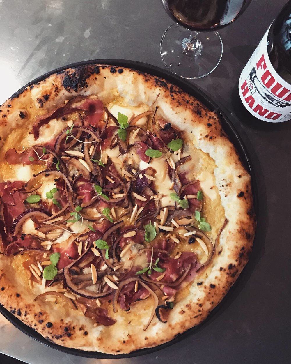 10-16 April - ~ Mugnaia ~⠀⠀White base of artichoke cream, gorgonzola, smoked mountain speck, crispy red onion, burnt almonds and extra virgin olive oil. ⠀⠀To match the character of this bold pizza, we match a hearty, comforting glass of our beloved Four in Hand Shiraz (Barossa).⠀