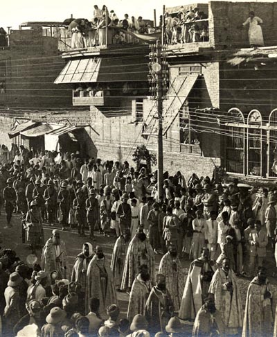 The celebration of the Christian Catholic feast of Corpus Christi in Baghdad in the 1920s. The patriarch, bishops, and priests of the Chaldeans [CatholicAssyrians], the most numerous of Iraq's Catholics, the Syriac Catholic and Armenian Catholic bishops are seen with their priests, deacons and students marching through the streets of Baghdad close to the old Christian Quarter of Agd al-Nasara. ( Text and photo courtesy of Wikipedia.)