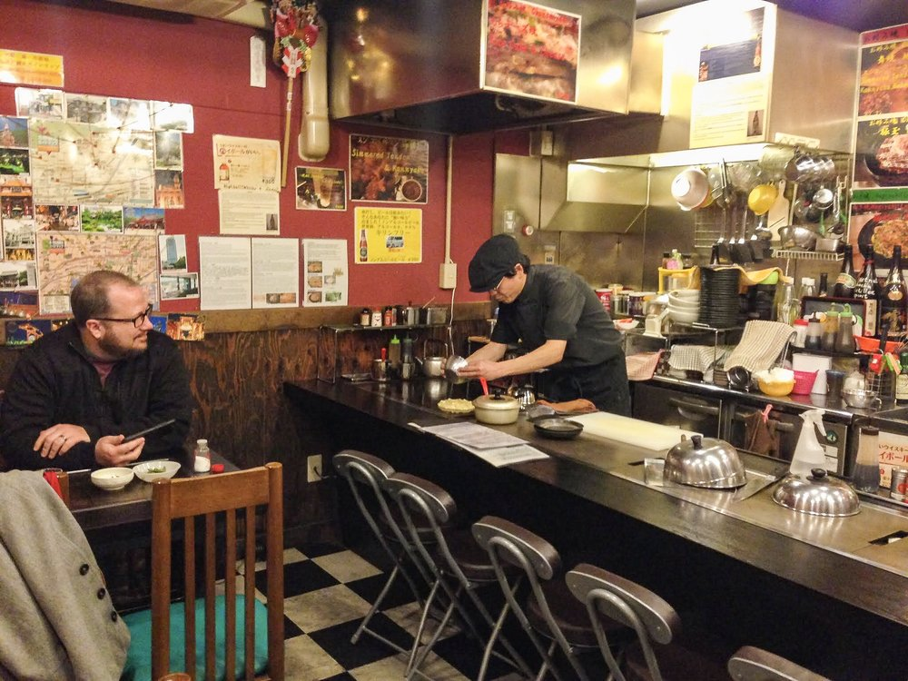 "Doing my best ""Bourdain"" in Kobe, Japan at Okonomiyaki Mai - where the incredibly welcoming owner grilled up the savory pancakes to order."