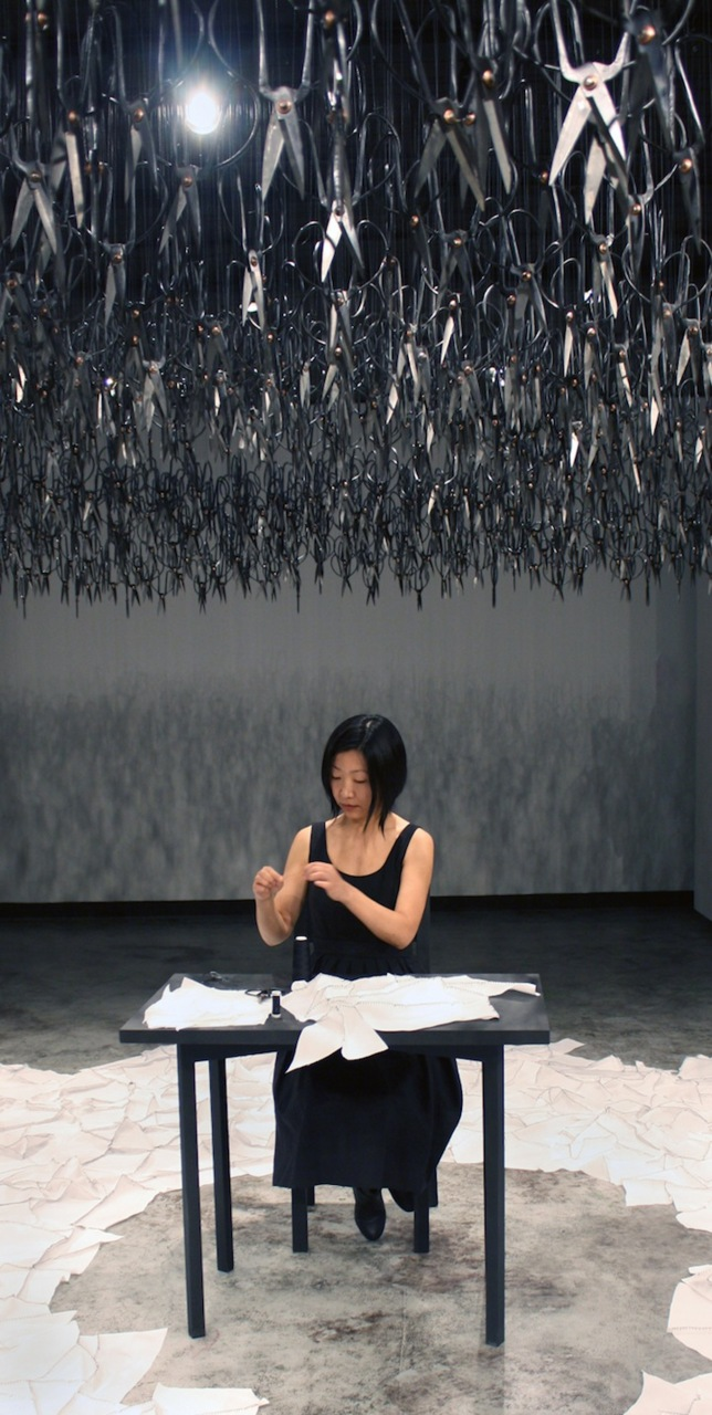 darksilenceinsuburbia :       Beili Liu  .   Imagine walking into a silent room where a woman is mending. Now imagine that she's sitting underneath 1,500 pairs of sharp Chinese scissors that are suspended from the ceiling, precariously pointed downwards. This was the idea behind  The Mending Project  by Beili Liu.    http://www.beililiu.com/index.html