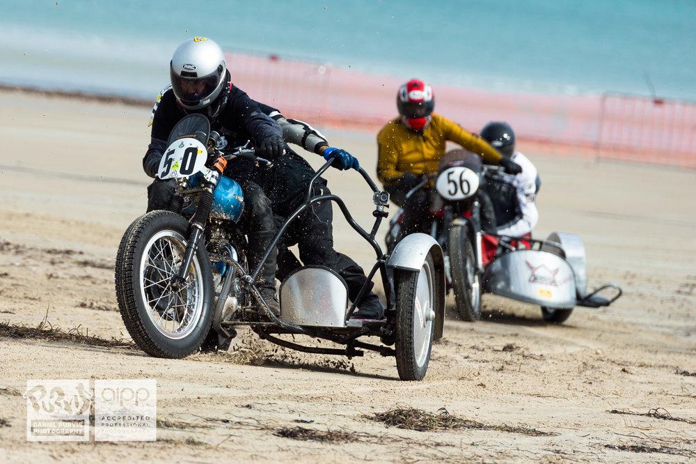 (50) Paul Dempsey / Carey Dechamps riding 1950 Triumph chased by (56) David Sigston / Vince Hitchman riding 1956 Norton/BSA, rounding final corner. © Daniel Purvis