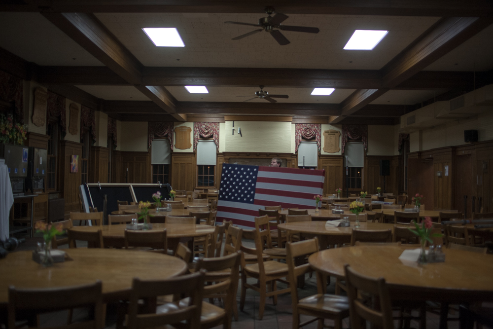 A worker removes a large American flag from the dining area at the Tilton School where Romney hosted a spaghetti dinner leading into the final days of the New Hampshire primary.