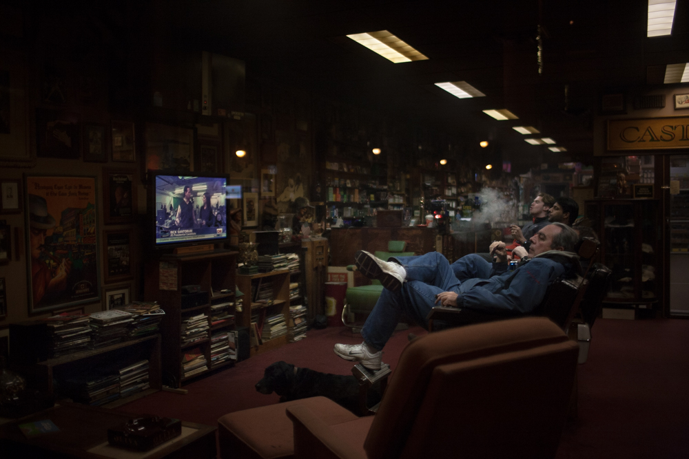Patrons of a cigar bar in Manchester watch an interview with Republican candidate Rick Santorum while New Gingrich ended his campaign next door at his campaign headquarters.