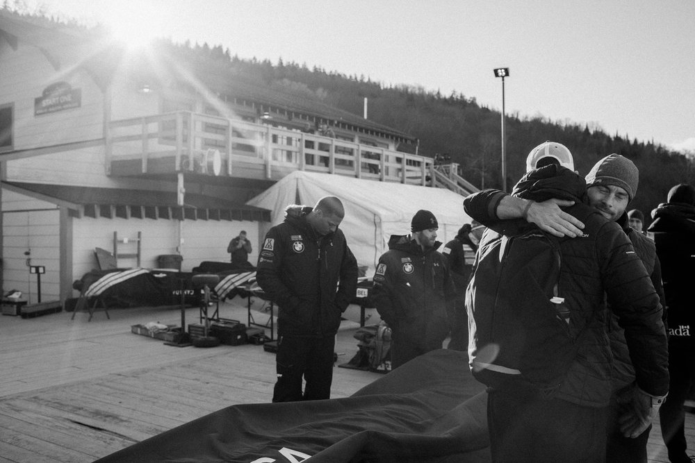 Two-time Olympic medalist, Steve Langton, receives a hug while waiting with members of the US National bobsled team for their turn during training runs down the track in Lake Placid, New York. Olympic veterans and hopefuls in bobsled and skeleton gathered in Lake Placid, New York leading up to the World Cup Bobsled and Skeleton races held November 9-10, 2017. Results from Lake Placid, one stop along the circuit, will help determine teams for the 2018 Winter Olympics in Pyeongchang, South Korea.