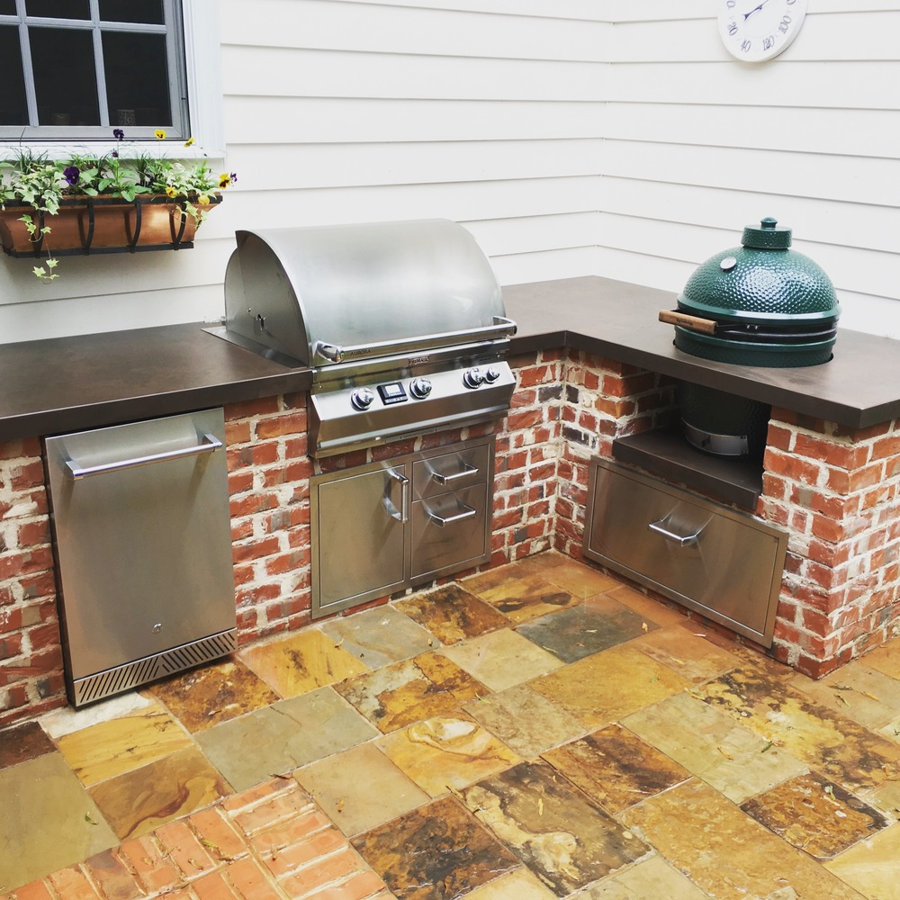 Custom grill island with large big green egg, firemagic grill, delta heat refrigerator and Dekton countertop