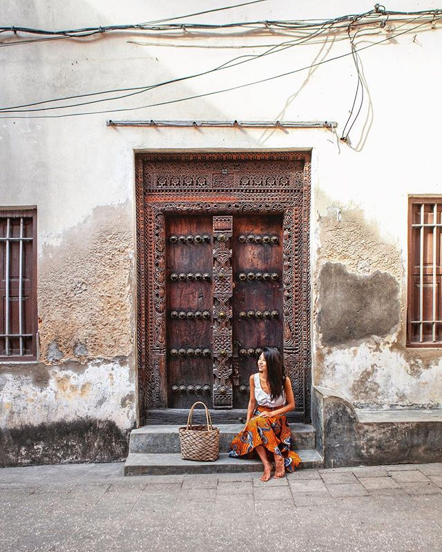 The prettiest door in Stone Town 🚪 Once the flourishing center of the spice route and slave trade, Stone Town has a colorful history of European and Arab rulers. . Walking around it was most apparent in the architecture, like this door that has Arab influences from its rectangular shape and intricate carvings but also Indian influences because of its brass studs which represent wealth. It's a @unesco World Heritage Site well worth preserving for the #doortraits alone ☺️