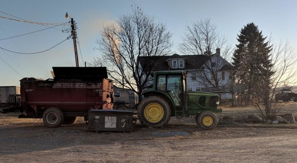 A farmer's home peeks behind their feed mixer and tractor. Image from author, 2018.