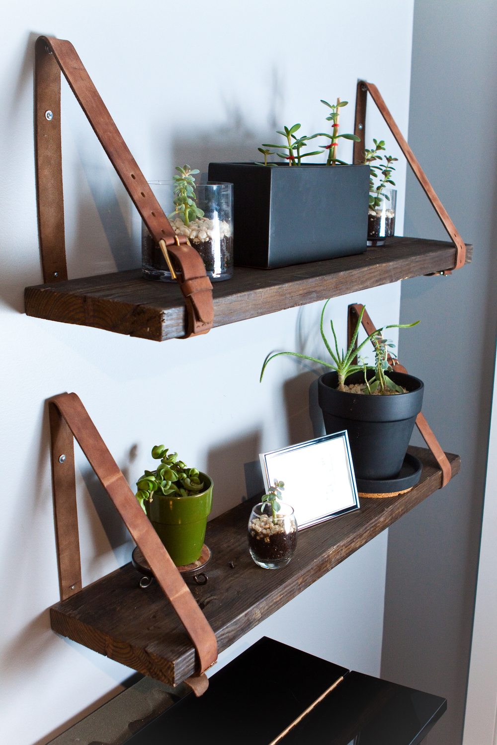 Distressed belts hold 2 reclaimed wood shelves in place for just the right touch in this eclectic space.