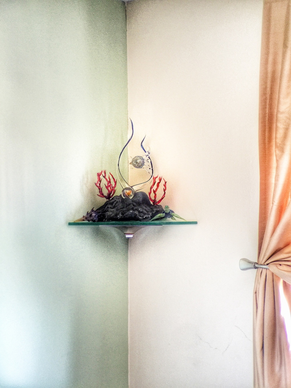 A small glass corner shelf was a perfect was to hold this families glass art.