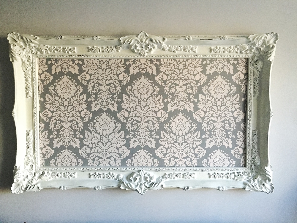 Our client fell in love with a damask stencil that we painted in custom colors and framed as a one of a kind statement over the sofa.