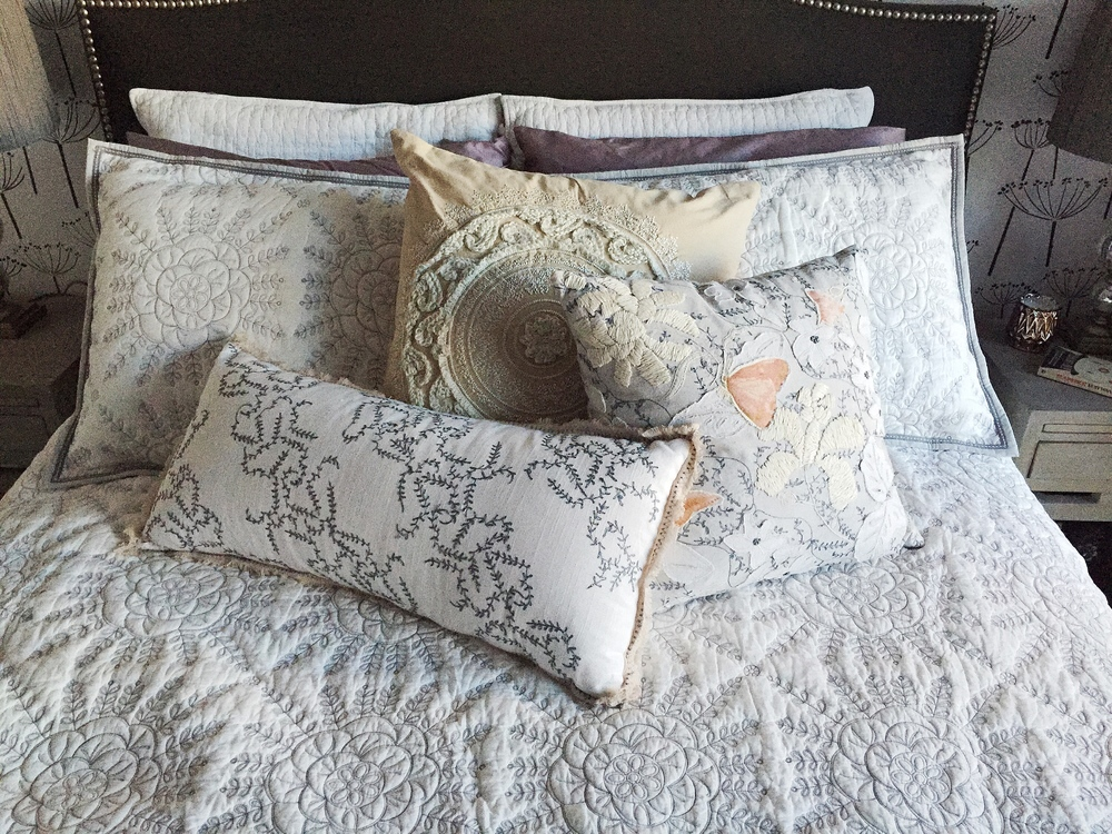 We chose an embroidered quilt and throw pillows for bedding, a pair of new night stands and matching table lamps to round out the accent wall.