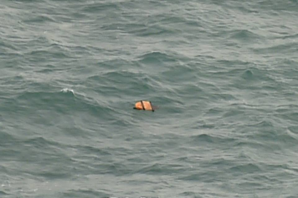 An orange-colored object is seen floating on waters of the official search area Tuesday (30 December 2014, reported around 1415 GMT+8).  This particular piece of debris does indeed look similar to an inflated life vest but we require high resolution images to verify this possibility