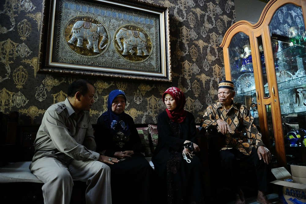 Relatives of Iriyanto, the captain of AirAsia Flight QZ8501, including his wife, Rr Widya Sukati Putri, gathered at his house in Surabaya, Indonesia, on 30 December 2014. Iriyanto's wife sits second from the right, in the red scarf