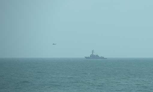 S naval vessel USS Sampson, seen here together with its search helicopter, is spotted near MV Swift Rescue's operating area
